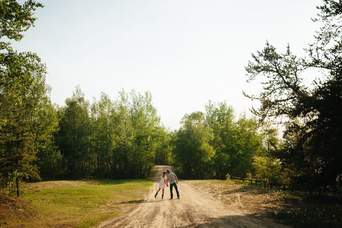 Couple walking down a gravel road holding hands, leaning in for a kiss.