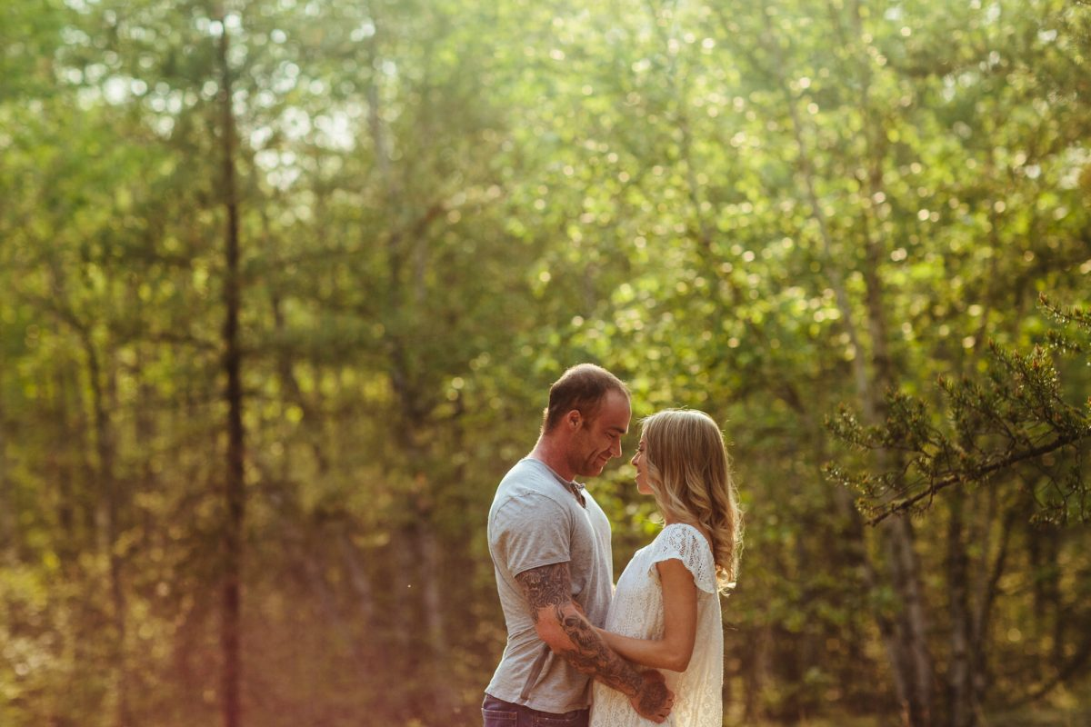 Roughley Originals Engagement Photography at Chump Lake, Alberta. Couple embracing in the trees with beautiful golden hour light shining upon them.